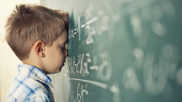 boy with head down on chalk board